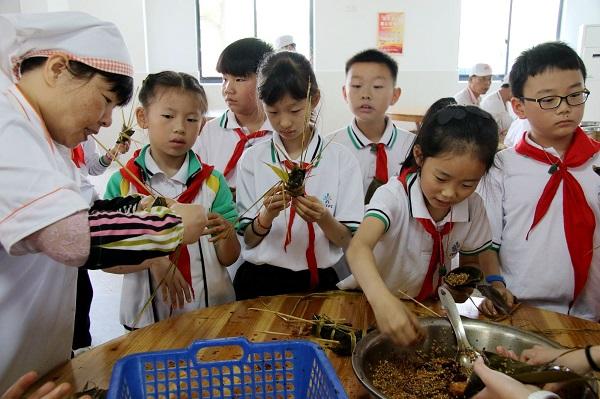 九亭四小非常注重传统节日,图为端午节,学生们在食堂阿姨的指导下,体验包粽子的乐趣,学校供图 - 万能看图王.jpg