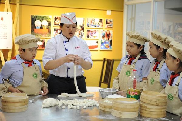 """3.古猗小学的学生们认真学习和体验""""南翔小笼""""制作过程(学校供图).JPG"""