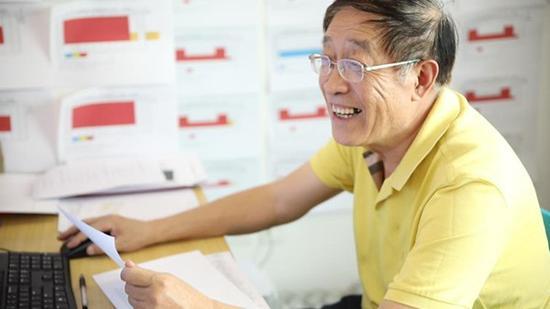 工作中的王佳彦,墙上是满满的排片表.jpg
