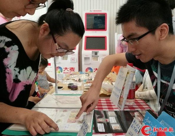 在市群艺馆一楼,王嘉轶向参观者介绍他的藏品。胡晓芒 摄 (1).jpg