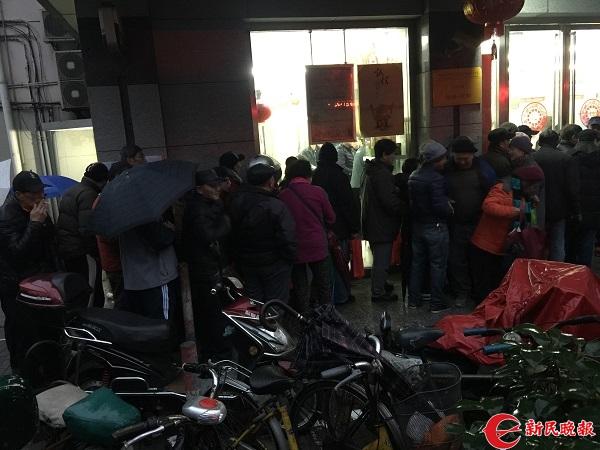 天还没有完全亮,曹杨新村邮政支局大厅也容纳不下所有排队的人.jpg
