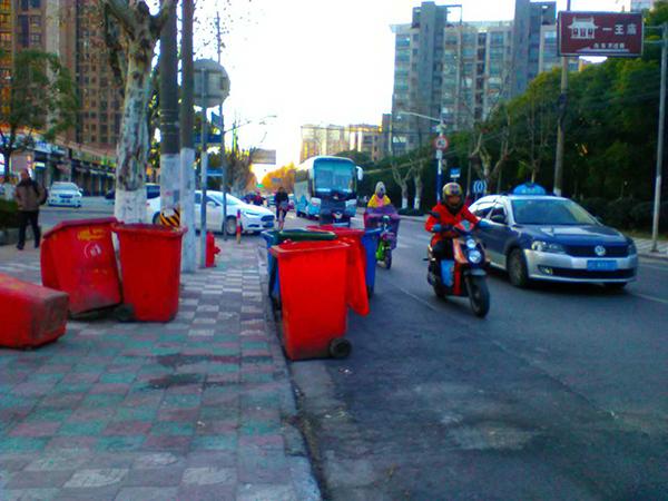 """由于垃圾桶""""侵占""""了非机动车道,来往的机动车只能驶向靠近机动车道,十分危险.jpg"""