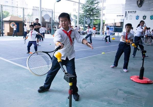 图:网球课上,每位学生都佩戴运动手环,老师不仅能实时掌握学生身体状况,还能根据数据个性化地调整运动强度和内容(校方供图) - 万能看图王.jpg