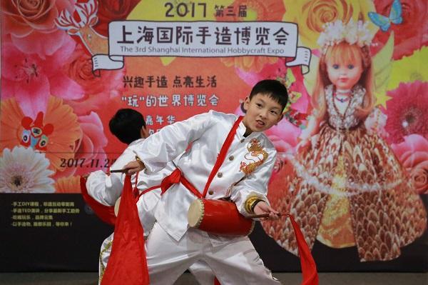 """图1:""""颛小鼓娃""""多次参加市级、区级各类演出活动,图为""""颛小鼓娃""""在上海国际手造博览会上向现场观众展示技艺。(校方供图).JPG"""