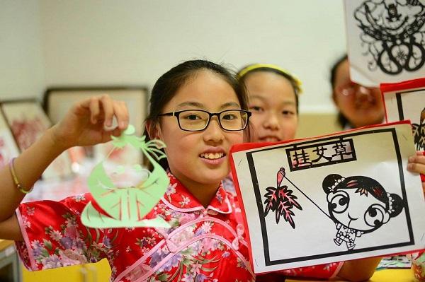 """图3:颛桥小学将民族文化教育融入到日常教学与校园文化活动之中,图为学校剪纸小能手在学校端午节活动中展示作品。 """"颛小鼓娃""""""""一剪美""""等优秀的民俗文化课程。(校方供图).jpg"""