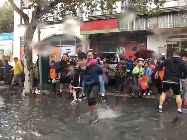 家长和老师们都趟着水 只为把孩子背入校园.jpg