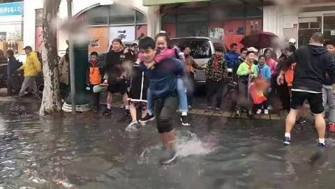 降雨后校门口现积水 热心人背着孩子入校门