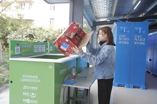东华大学菜鸟驿站,大学生将收到的快递纸盒现场拆封,把纸盒投入回收箱.jpg