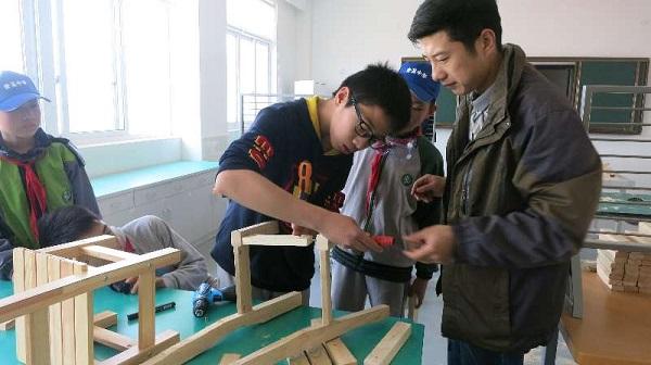 """项大勇老师在""""我是小鲁班""""木工课上指导学生拼接小板凳【校方供图】 - 万能看图王.jpg"""