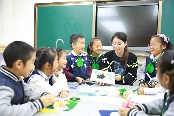 东华附校已开设的拓展型特色课程达80余门。图为学生们围坐在老师身旁,学习创意布贴画。(校方供图).jpg