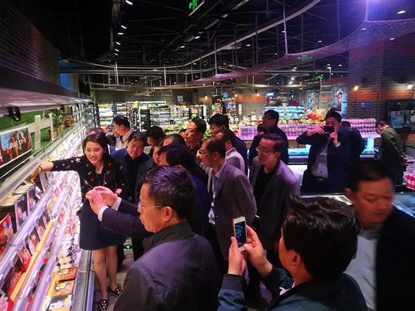 盒马工作人员给县干部介绍货架上来自全球的生鲜商品.JPG