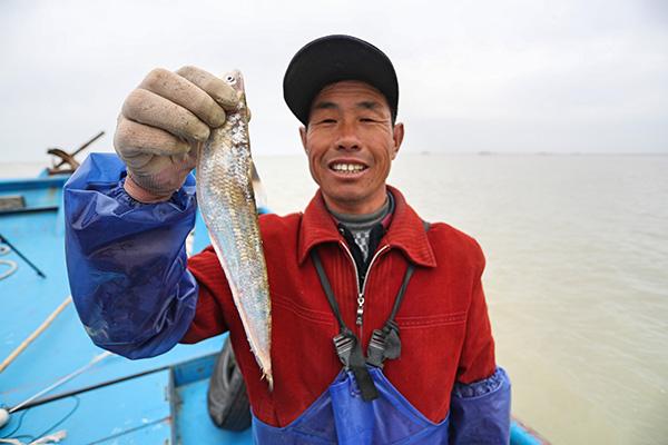 渔民手上拎着一条刚刚捕捞到的长江刀鱼.jpg