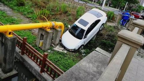 这个司机开车有点猛 撞破护栏差点冲进河道里