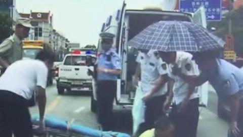骑车老伯路口被撞倒 途经民警在车流中为其撑伞遮阳