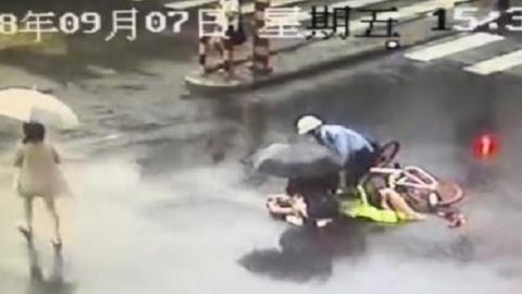 暖心:老人雨天骑车摔倒 热心警民为其撑伞