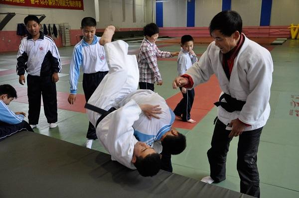 柔道课上,专业教练正耐心地指导学生们掌握动作要领(学校供图).JPG