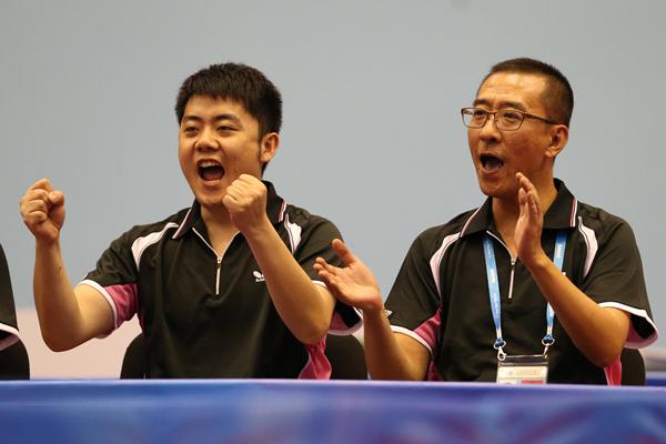 2013年7月12日 中国队教练丁松(右)庆祝中国队得分。当日,在俄罗斯喀山进行的第27届世界大学生夏季运动会乒乓球男子团体决赛中,中国队以3比0战胜日本队,获得冠军。_副本.jpg
