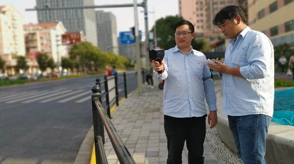 """志愿者手持高清测速仪在32个路口为进博会""""稳守安全"""""""