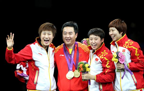 8月7日,中国队选手丁宁(左一)、李晓霞(右一)和郭跃(右二)在颁奖仪式上把金牌挂在女队主教练施之皓脖子上。_副本.jpg
