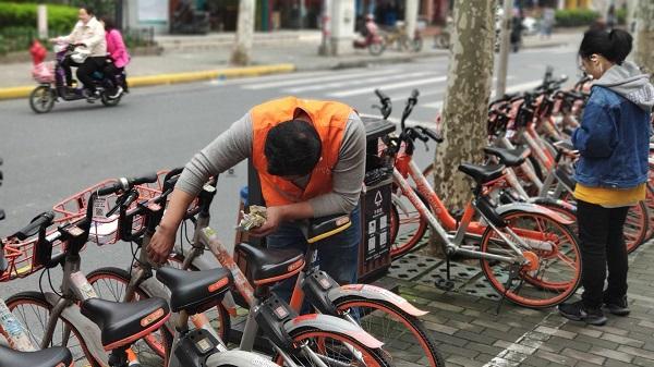 摩拜一线运维人员街头清理小广告.jpg