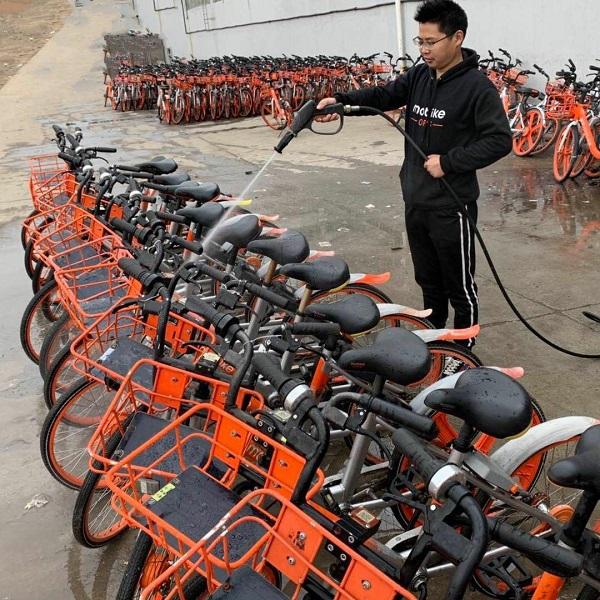 运维人员用水枪深度清洁单车.jpg