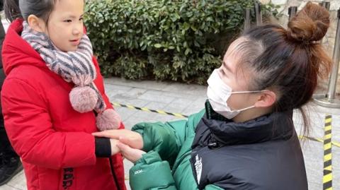 寒风中,幼儿园老师把每个孩子的小手捂进自己的掌心