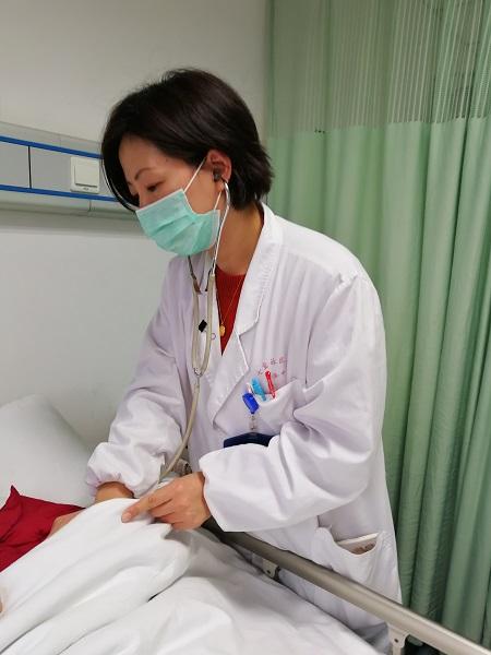竺国芳在给病人检查身体.jpg