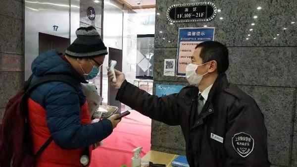 配图:物业工作人员为复工白领测体温(采访对象供图).jpg