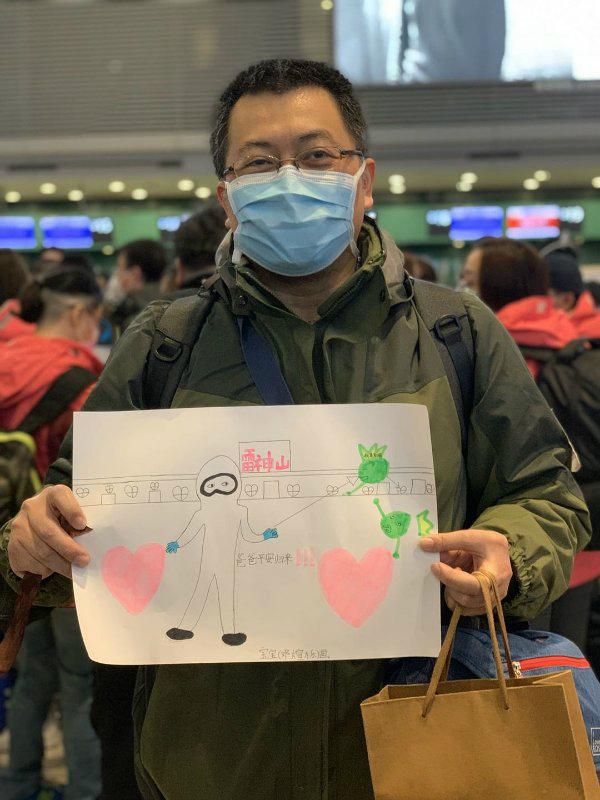 图说:邓玉海拿着女儿的画作 作者供图.jpg