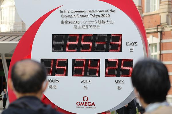 当地市民驻足查看设置在日本东京站前的东京奥运会和残奥会的倒计时电子钟-新华社downLoad-20200326120447_副本.jpg