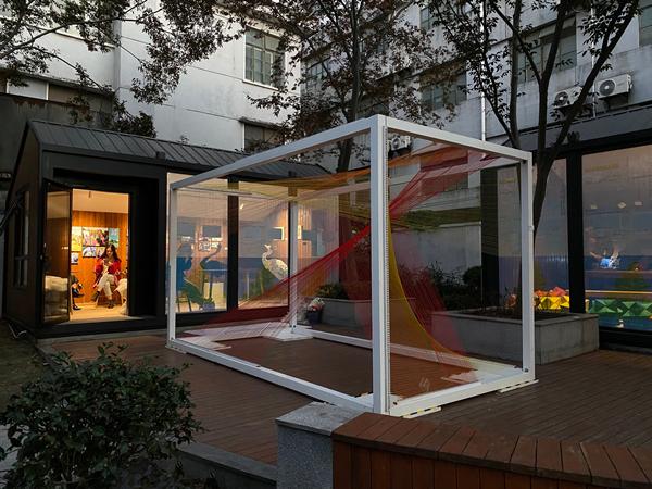 """在高境镇的宝山众文空间座落在三门路华润万家右侧,由两个呈L型的集装箱体小空间组成,因为是一个角落,所以2020年的展览名称就叫""""艺术角:高境社区展"""",这次展览将单孔透材料的海报重复张贴在玻璃墙,两个小空间布置着作品,展览期间晚上也亮着灯,原先一个很平常的角落,有艺术作品烘托,变得格外的朦胧迷人。_副本.jpg"""