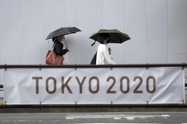 行人走过日本东京街头宣传奥运会的标语-新华社_副本.jpg